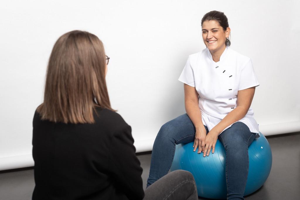 Une sage femme et sa patiente assises sur des balles de fitness
